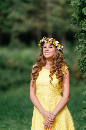 Portrait young girl in yellow dress with Flower wreath for head. Walking in park, Warm summer day. 写真素材