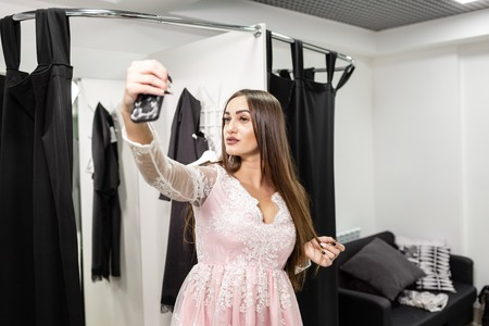 Young woman make a selfie in a new pink dress. Shopping clothes in mall or clothing store. Sale, fashion, consumerism concept 写真素材