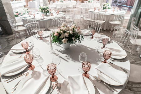 Interior of restaurant for wedding dinner, ready for guests. Round Banquet table served. Decorated with floral arrangement. Dishes, wine glasses and napkins. Catering concept.