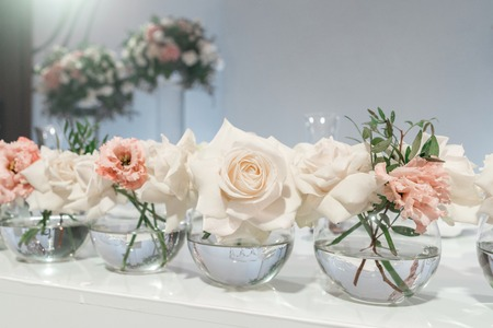 Small flower arrangements in ball glass vases. The table of the newlyweds. Interior of restaurant for wedding dinner, ready for guests. Catering concept.