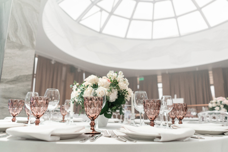 Wine glasses on round Banquet table served. Interior of restaurant for wedding dinner, ready for guests. Decorated with floral arrangement. Dishes, wine glasses and napkins. Catering concept.