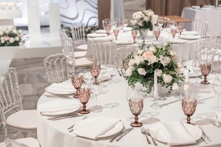 Kompozycja kwiatowa na środku stołu. Wnętrze restauracji na obiad weselny, gotowe dla gości. Okrągły stół bankietowy serwowany. Koncepcja cateringu.