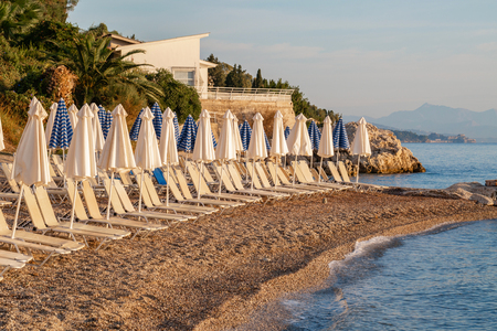 Summer sunrise on coast, Corfu island, Greece. Beach with Sunbeds and umbrellas with perfect views of the mainland Greece mountains.