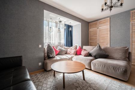 Rusia, Nizhny Novgorod - 26 de abril de 2019: Apartamento privado. Sala de estar moderna con sofá de cuero, sillón, mesa de centro de madera y Tv. almohadas en un acogedor sofá y lámparas. Diseño de interiores Editorial