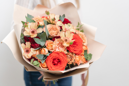 Beautiful bouquet of mixed flowers in womans hands. the work of the florist at a flower shop. Delicate Pastel color. Fresh cut flower. Red and peach color