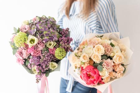 Dwa piękne bukiety mieszanych kwiatów w rękach kobiety. praca kwiaciarni w kwiaciarni. Delikatny pastelowy kolor. Świeży kwiat cięty.
