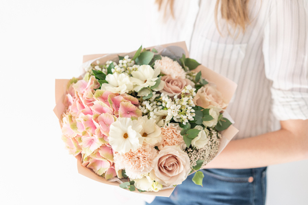Delicate bouquet of mixed flowers in womans hands. the work of the florist at a flower shop. Delicate Pastel color. Fresh cut flower. White and pink color Reklamní fotografie - 122608681