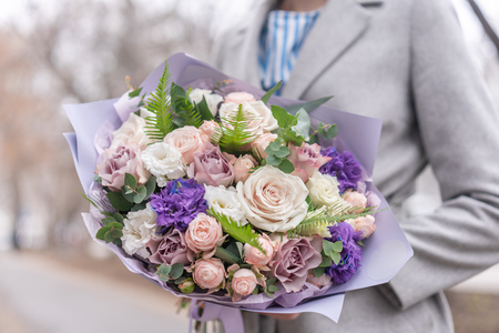 Nice bouquet of mixed flowers in woman hand. Pink and white color. the work of the florist at a flower shop. Delicate Pastel color. Fresh cut flower. Reklamní fotografie - 122608685
