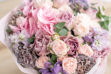 Beautiful bouquet of mixed flowers on wooden table. the work of the florist at a flower shop. Delicate Pastel color. Fresh cut flower. Pink and lilac color Stockfoto