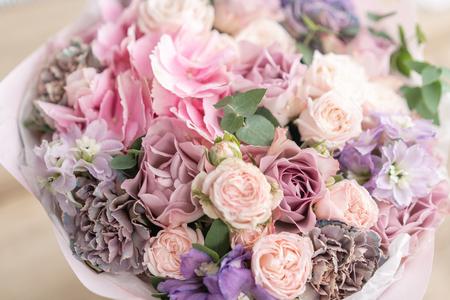 Mooi boeket van gemengde bloemen op houten tafel. het werk van de bloemist in een bloemenwinkel. Delicate pastelkleur. Verse snijbloem. Roze en lila kleur