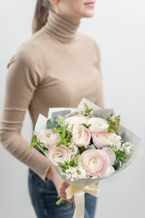 Mono bouquet of roses. Delicate bouquet of mixed flowers in womans hands. the work of the florist at a flower shop. Delicate Pastel color. Fresh cut flower. Reklamní fotografie - 122608692
