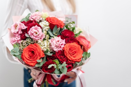 Beautiful bouquet of mixed flowers in womans hands. the work of the florist at a flower shop. Delicate Pastel color. Fresh cut flower. Red and pink color