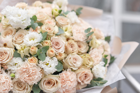 Large Beautiful bouquet of mixed flowers in woman hand. Pink and white color. the work of the florist at a flower shop. Delicate Pastel color. Fresh cut flower. Reklamní fotografie - 122608698