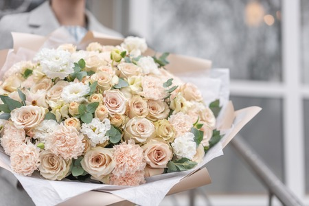 Large Beautiful bouquet of mixed flowers in woman hand. Pink and white color. the work of the florist at a flower shop. Delicate Pastel color. Fresh cut flower. Reklamní fotografie - 122608699