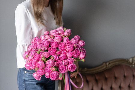 Bush roses, Pink peony in womans hand. Beautiful peony flower for catalog or online store. Beautiful bouquet. Floral shop concept . Fresh cut Flowers delivery Reklamní fotografie - 122608719