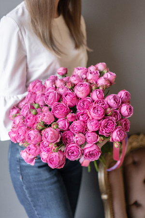 Bush roses, Pink peony in womans hand. Beautiful peony flower for catalog or online store. Beautiful bouquet. Floral shop concept . Fresh cut Flowers delivery