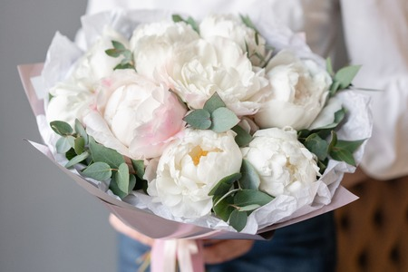 White peonies with eucalyptus in womans hand. Beautiful peony flower for catalog or online store. Beautiful bouquet. Floral shop concept . Fresh cut Flowers delivery