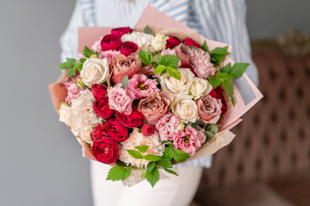 Beautiful bouquet of mixed flowers in woman hand. the work of the florist at a flower shop. Delicate Pastel color. Fresh cut flower. 版權商用圖片