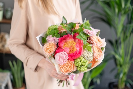 Small Beautiful bouquet of mixed flowers in woman hand. Floral shop concept . Beautiful fresh cut bouquet. Flowers delivery