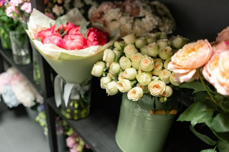 Flower shop concept. Glass vases with different flowers on the shelves of the refrigerator showcases. Abstract background of floral. Flowers composition.