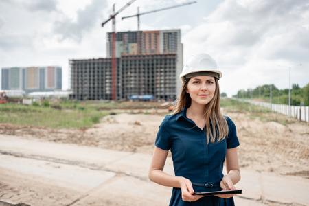 Ingegnere edile femminile. Architetto con un computer tablet in un cantiere edile. Sguardo della giovane donna a porte chiuse, posto del cantiere sullo sfondo. Concetto di costruzione