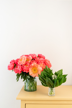 Coral peonies and spring lilies of the valley in a glass vase on wooden table.. Beautiful peony flower for catalog or online store. Floral shop concept . Beautiful fresh cut bouquet. Flowers delivery.