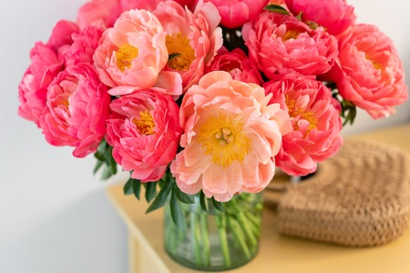 Coral peonies in a glass vase and wicker bag on wooden table.. Beautiful peony flower for catalog or online store. Floral shop concept . Beautiful fresh cut bouquet. Flowers delivery. Copy space Foto de archivo