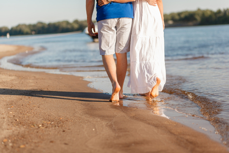 Feet in the water summer. Young barefoot couple walking along the beach. Love story. Waves and sand. Concept of rest.
