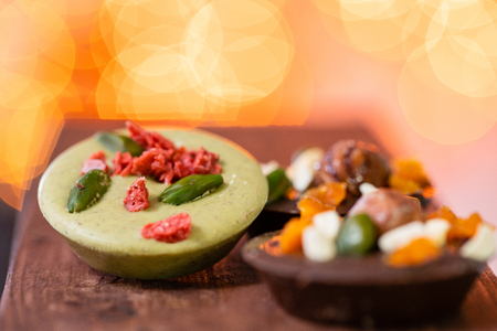 Christmas theme. Handmade chocolates candy. Mini chocolate dessert covered with nuts and dried fruits. Garland lamps bokeh on background.