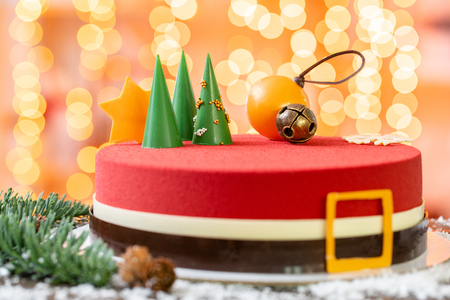 Mini mousse pastry dessert covered with red velour. Garland lamps bokeh on background. Modern european cake. French cuisine. Christmas theme. Copy space