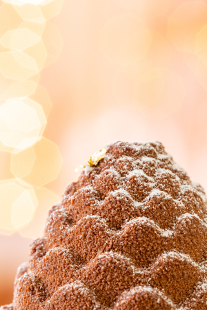 Dessert in the form of Christmas cone. Mini mousse pastry dessert covered with velour. Garland lamps bokeh on background. Modern european cake. French cuisine. Christmas theme. Copy space.
