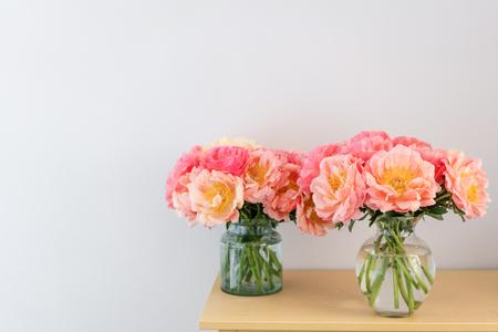 Peonías de coral en un jarrón de cristal. Hermosa flor de peonía para catálogo o tienda online. Concepto de tienda floral. Hermoso ramo recién cortado. Entrega de flores.