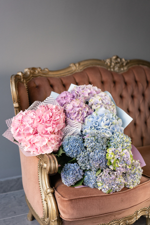 Bouquets of hydrangeas lying on vintage sofa. Small Beautiful bouquet of hydrangea flowers. Floral shop concept . Beautiful fresh cut bouquet. Flowers delivery Stockfoto