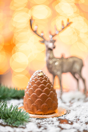 Dessert in the form of Christmas cone. Mini mousse pastry dessert covered with velour. Garland lamps bokeh on background. Modern european cake. French cuisine. Christmas theme. Copy space