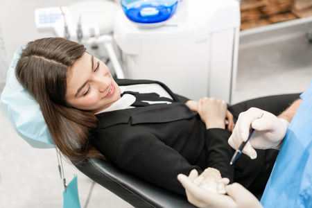 Young beautiful woman in the dentist chair at dental clinic. Medicine, health, stomatology concept. dentist treating a patient. Woman smiling