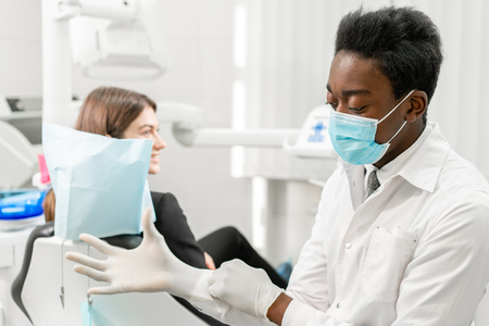 The doctor puts on rubber gloves. Young African male dentist with a patient. Woman in the dentist chair at dental clinic. Medicine, health, stomatology concept. dentist treating a patient.