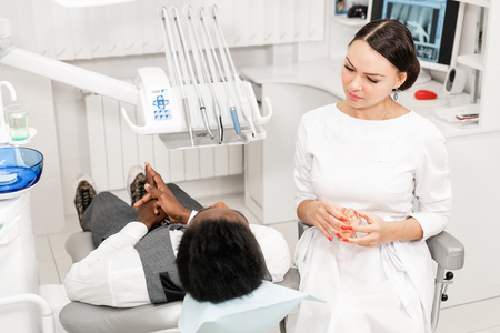 Young woman dentist treating root canals in the dental clinic. Young African American male with bad teeth lying on dentist chair with open mouth. Imagens