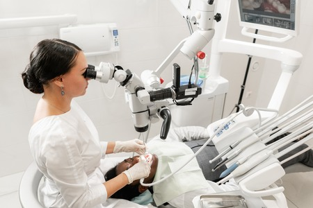 Modern equipment microscope in dental office. Young woman dentist treating root canals. Man patient lying on dentist chair with open mouth. Medicine, dentistry and health care concept.