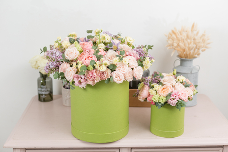 Two Beautiful spring bouquets in head box. Arrangement with mix flowers. The concept of a flower shop, a small family business. Work florist. copy space