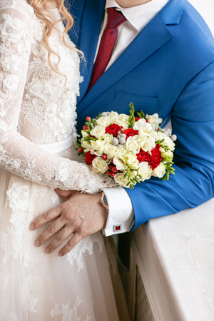 Bride and groom hold bridal bouquet close up. red and white roses, freesia, brunia decorated.