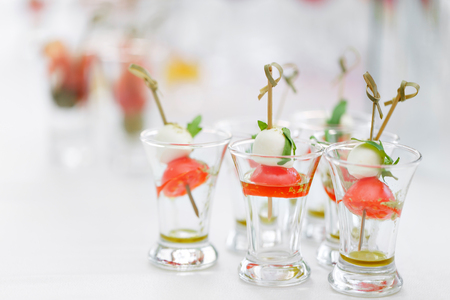 Appetizer, Caprese. Cherry tomatoes,mozzarella and Basil on skewers. . Pesto sauce. Buffet at the gala dinner. Assortment of canapes. Banquet service.