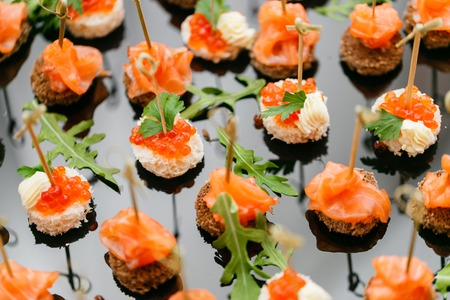 Buffet at the gala dinner. Assortment of canapes. Banquet service. catering food, snacks with salmon and caviar. rye, wheat bread.