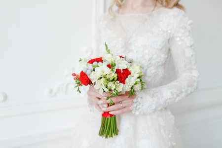 Bride hold bridal bouquet close up. red and white roses, freesia, brunia decorated. Stock Photo