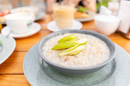 Breakfast and coffee in the summer cafe. Fresh oatmeal porridge with apples, honey, nuts and cinnamon close up for healthy breakfast