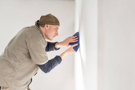 Young repairman aligns with plastic spatula. Worker glueing wallpapers on concrete wall. Repair the apartment. Home renovation concept. White Wallpaper for paint Foto de archivo - 124600949
