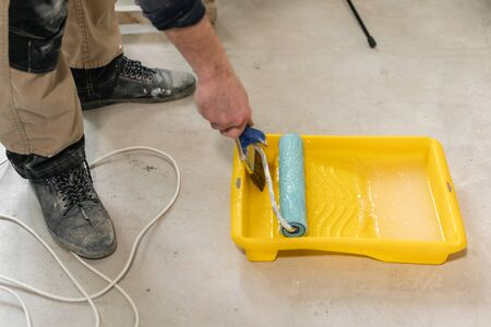 Young repairman smear on wall glue with a roller. . Worker glueing wallpapers on concrete wall. Repair the apartment. Home renovation concept. White Wallpaper for paint Foto de archivo - 124600951