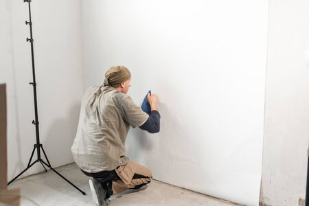 Young repairman aligns with plastic spatula. Worker glueing wallpapers on concrete wall. Repair the apartment. Home renovation concept. White Wallpaper for paint