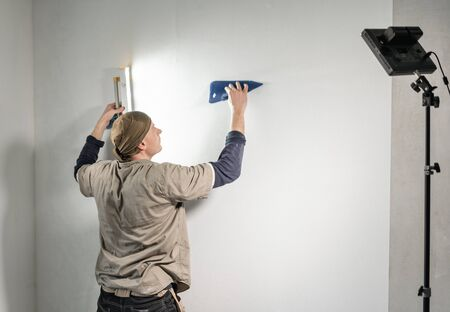 Young repairman aligns with plastic spatula. Worker glueing wallpapers on concrete wall. Repair the apartment. Home renovation concept. White Wallpaper for paint Foto de archivo - 124600956
