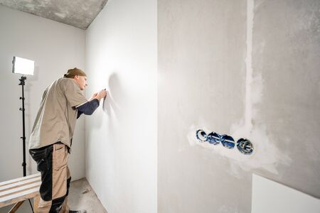 Young repairman aligns with plastic spatula. Worker glueing wallpapers on concrete wall. Repair the apartment. Home renovation concept. White Wallpaper for paint Foto de archivo - 124601004