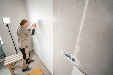 Young repairman aligns with plastic spatula. Worker glueing wallpapers on concrete wall. Repair the apartment. Home renovation concept. White Wallpaper for paint Foto de archivo - 124513221